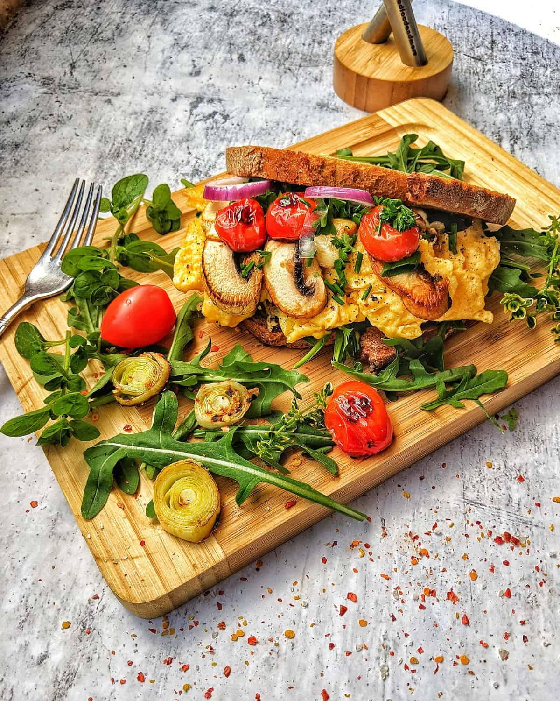 Ein dekaratives Rührei Sandwich mit vielen Veggies auf einem Holzbrett.