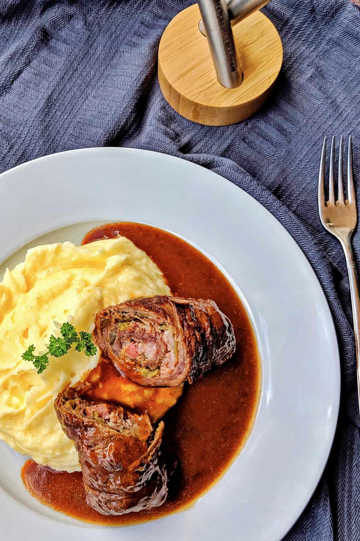 Ein weisser Teller mit einer aufgeschnittenen Roulade, Soße und Kartoffelpüree.