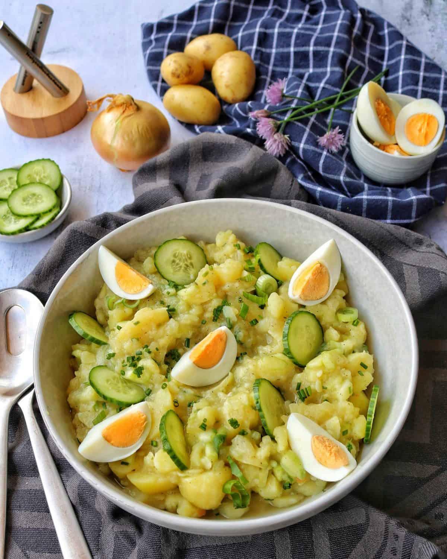 Eine große helle Schale mit Kartoffelsalat. Im Hintergrund Deko.