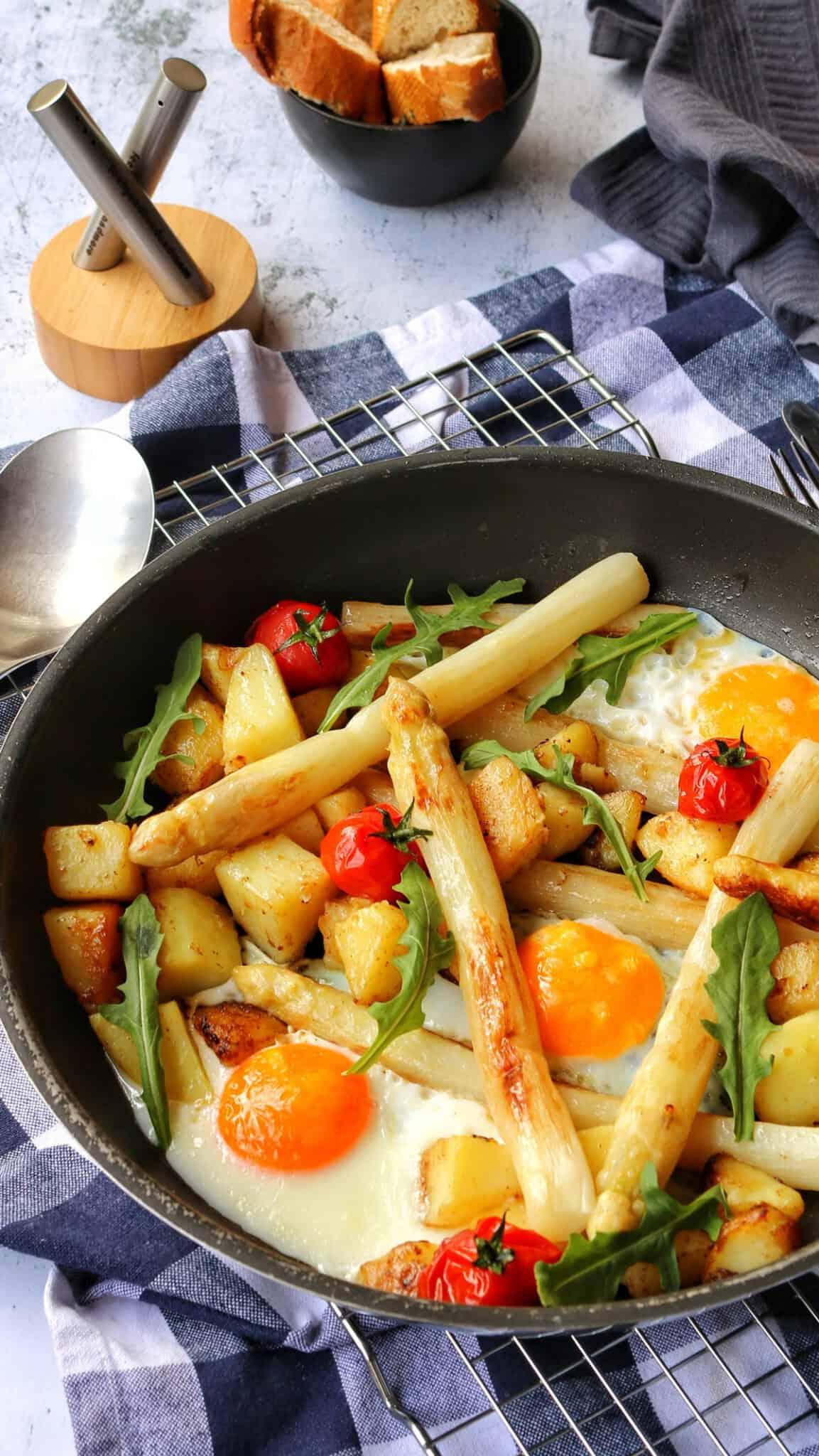 Eine Pfanne mit Spargel, Kartoffeln, Spiegelei, Kirschtomaten und Rucola. Im Hintergrund Deko