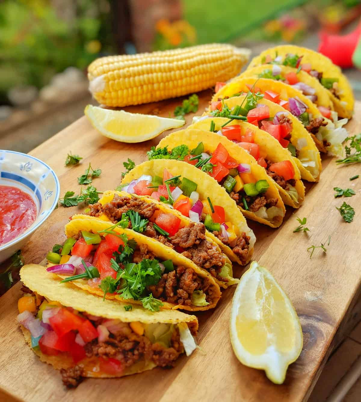 Ein Holzbrett auf dem Tacos mit Chili con Carne aufgereiht sind.