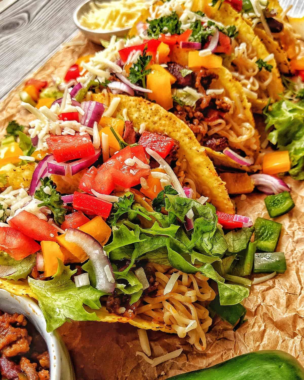 Tacos mit Ramen Nudeln und Chili con Carne aufgereiht auf einem Backpapier.