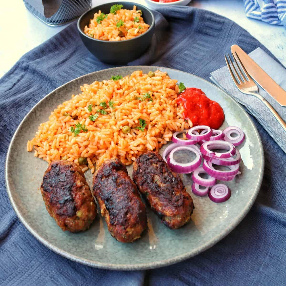 Ein gemusterter Teller mit Cevapcici und Djuvec Reis. Im Hintergrund ein Schälchen Reis.