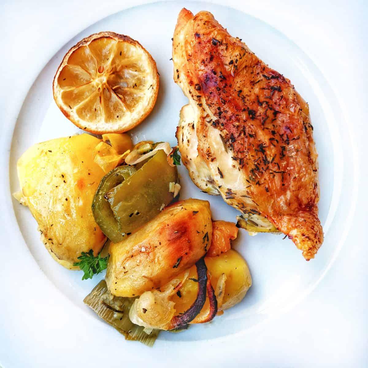 Ein weisser Teller mit mit Hähnchen, Kartoffeln und Gemüse.