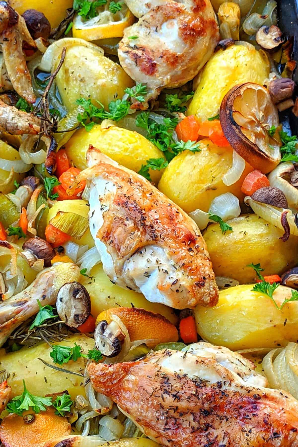 Eine Nahaufnahme der Zutaten von den Hähnchen, Kartoffeln und Gemüse aus dem Backofen.