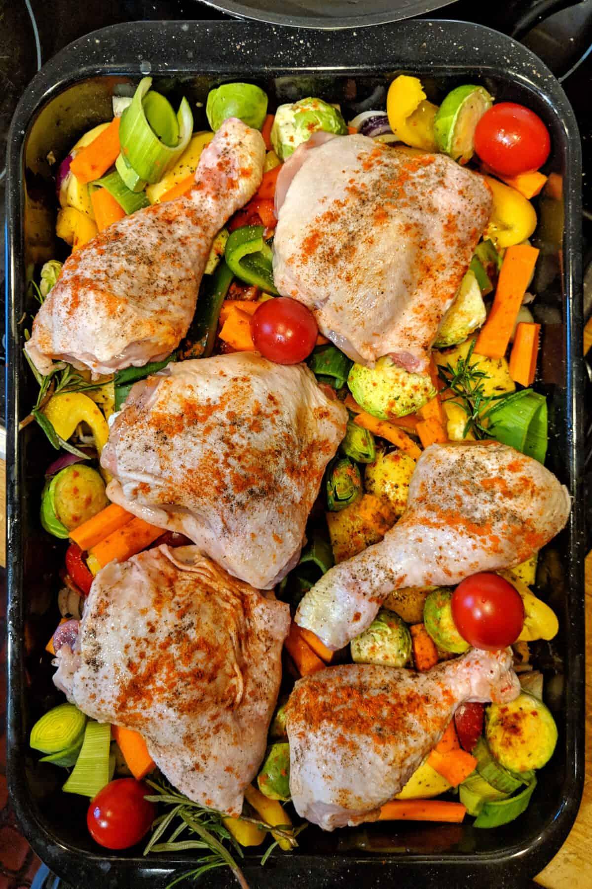 Eine Auflaufform mit Ofen gebackenes Hähnchen mit Gemüse und Kartoffeln vor dem Backen im Backofen.