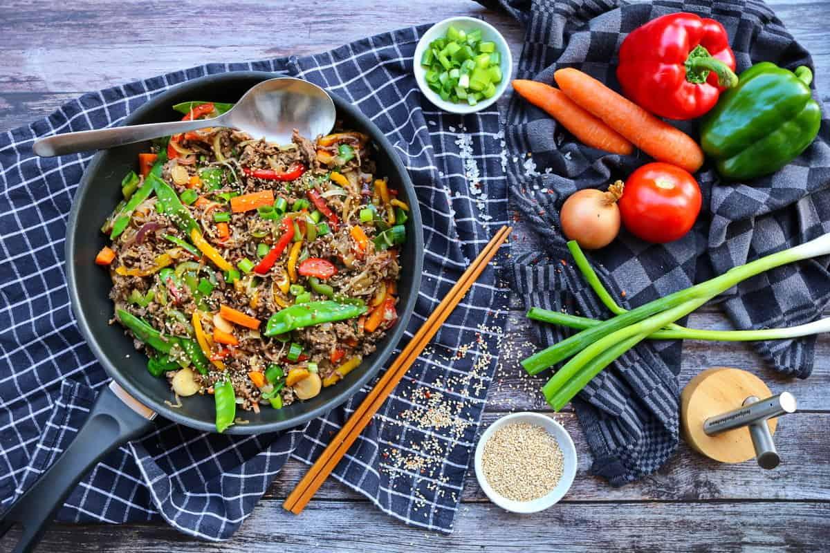 Eine Asia Reispfanne mit Gemüse und Rinderhack. Daneben Gemüse als Deko.