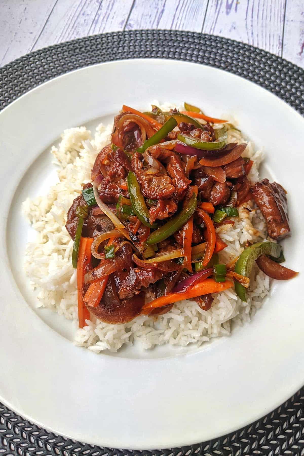 Ein weisser Teller mit Rindergeschnetzeltem mit buntem Gemüse und Reis.