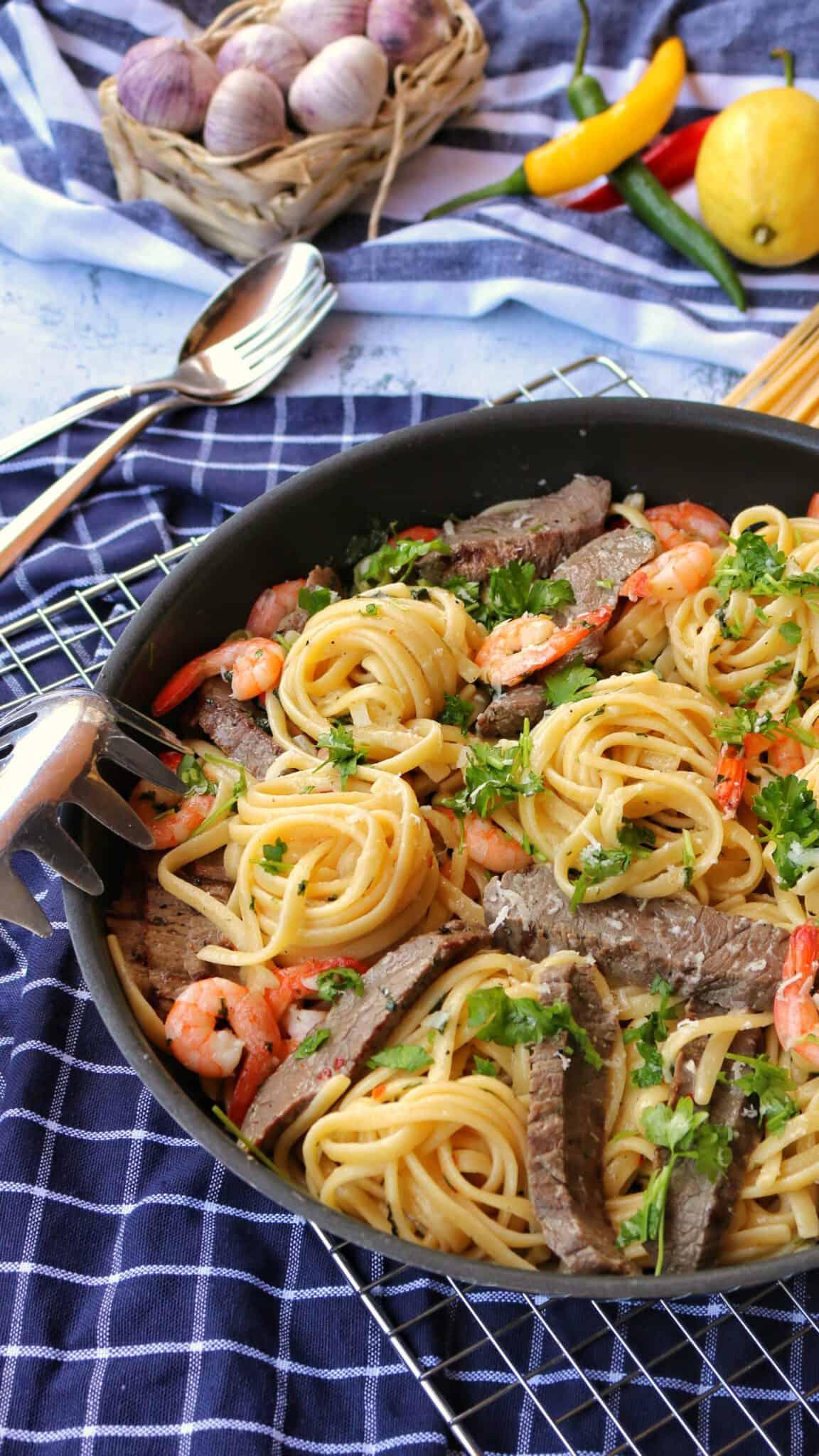 Eine Pfanne mit Spaghetti Aglio Olio mit Scampi und Steakstreifen. Im Hintergrund Deko.