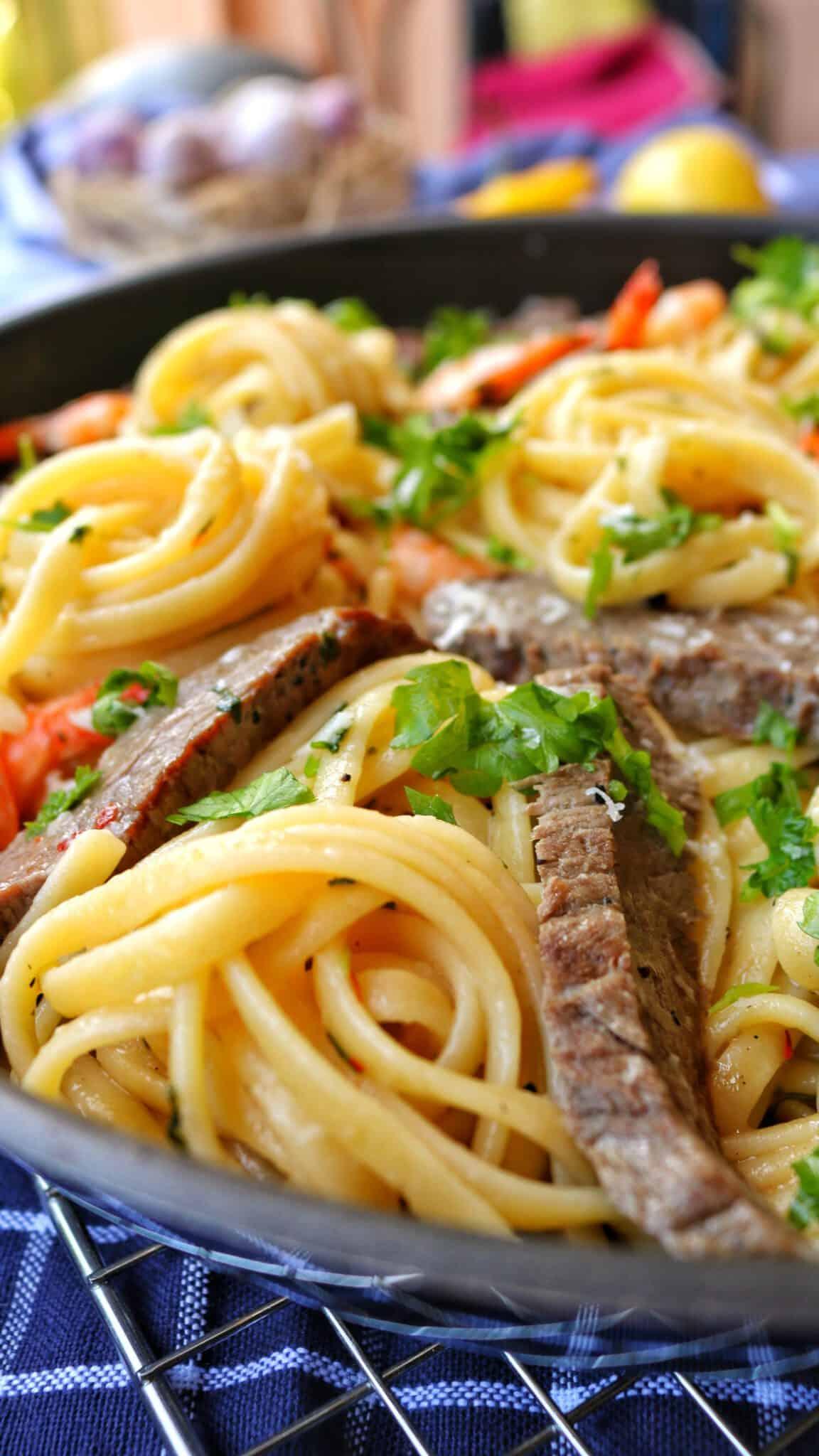 Eine Pfanne mit Spaghetti Aglio Olio mit Scampi und Steakstreifen.