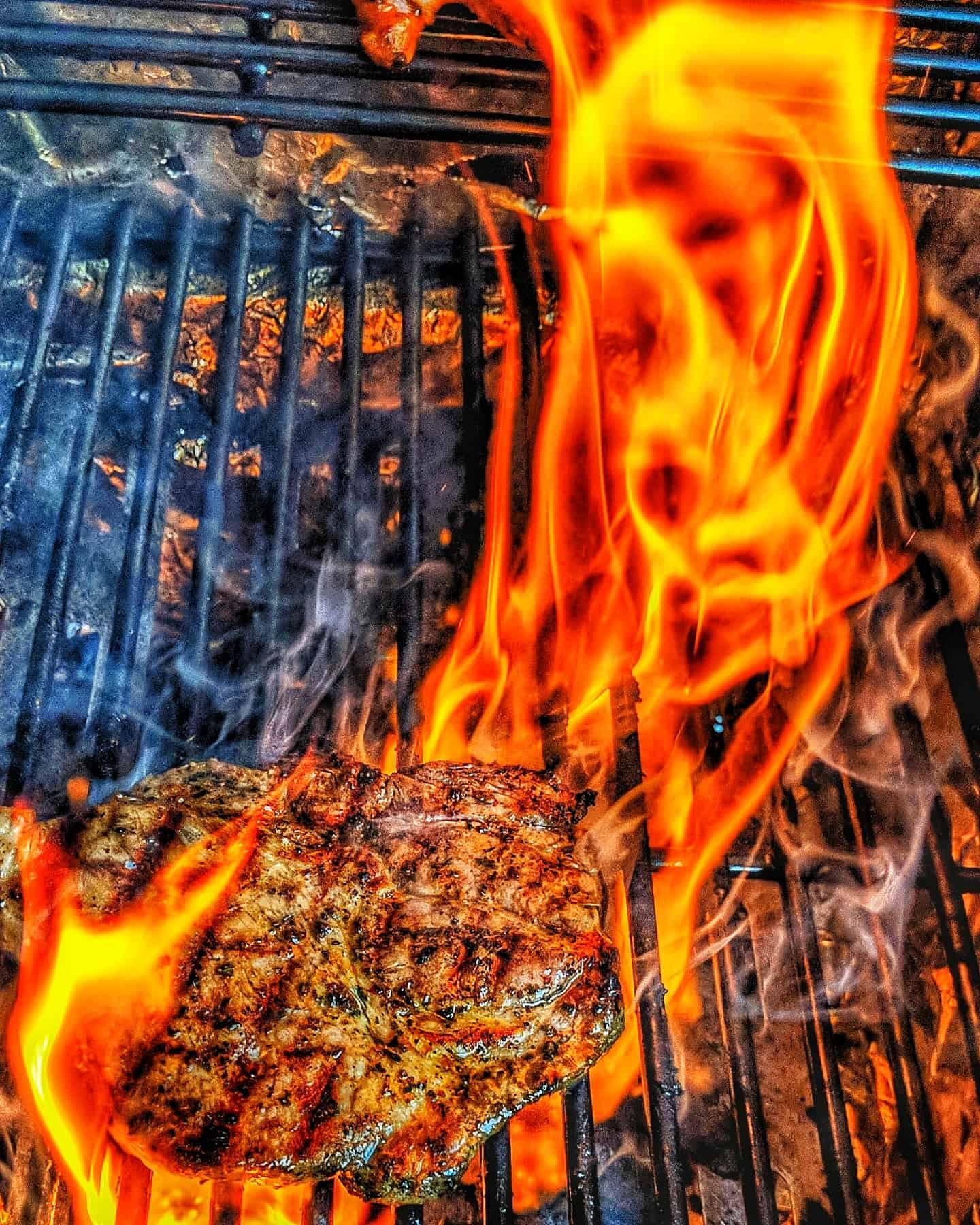 Ein Steak mit Flammen auf einem Grill.