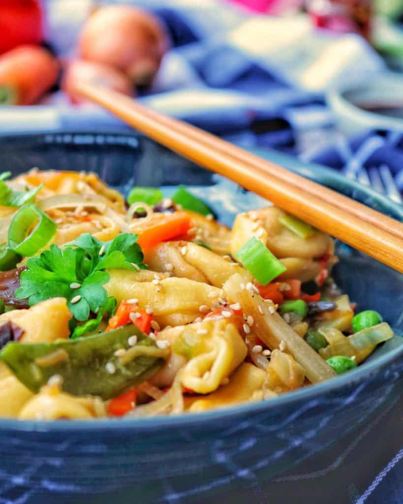 Eine Schüssel mit Tortellini und Asia-Gemüse. Im Hintergrund Deko.