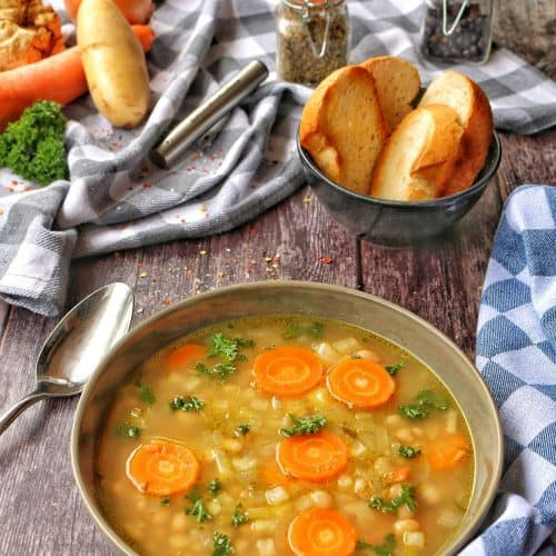 Ein Teller Weiße Bohnensuppe. Im Hintergrund Brot und Deko.