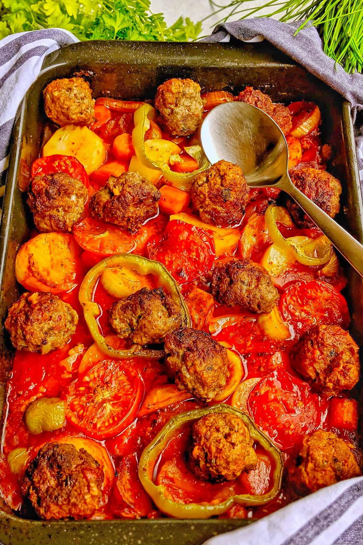 Eine Auflaufform mit Gebackene Kartoffeln in Tomatensoße mit Hackbällchen und Gemüse.