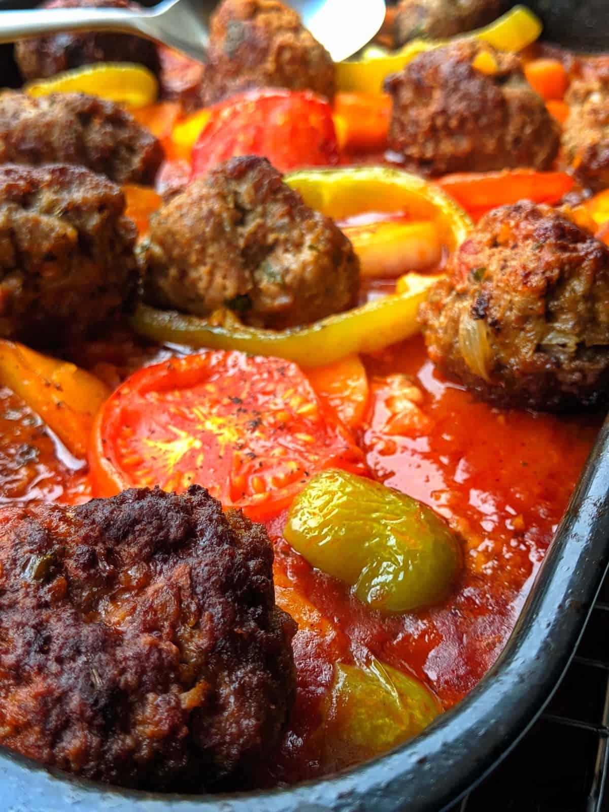 Eine Nahaufnahme von einer Auflaufform mit Gebackene Kartoffeln in Tomatensoße mit Hackbällchen und Gemüse.