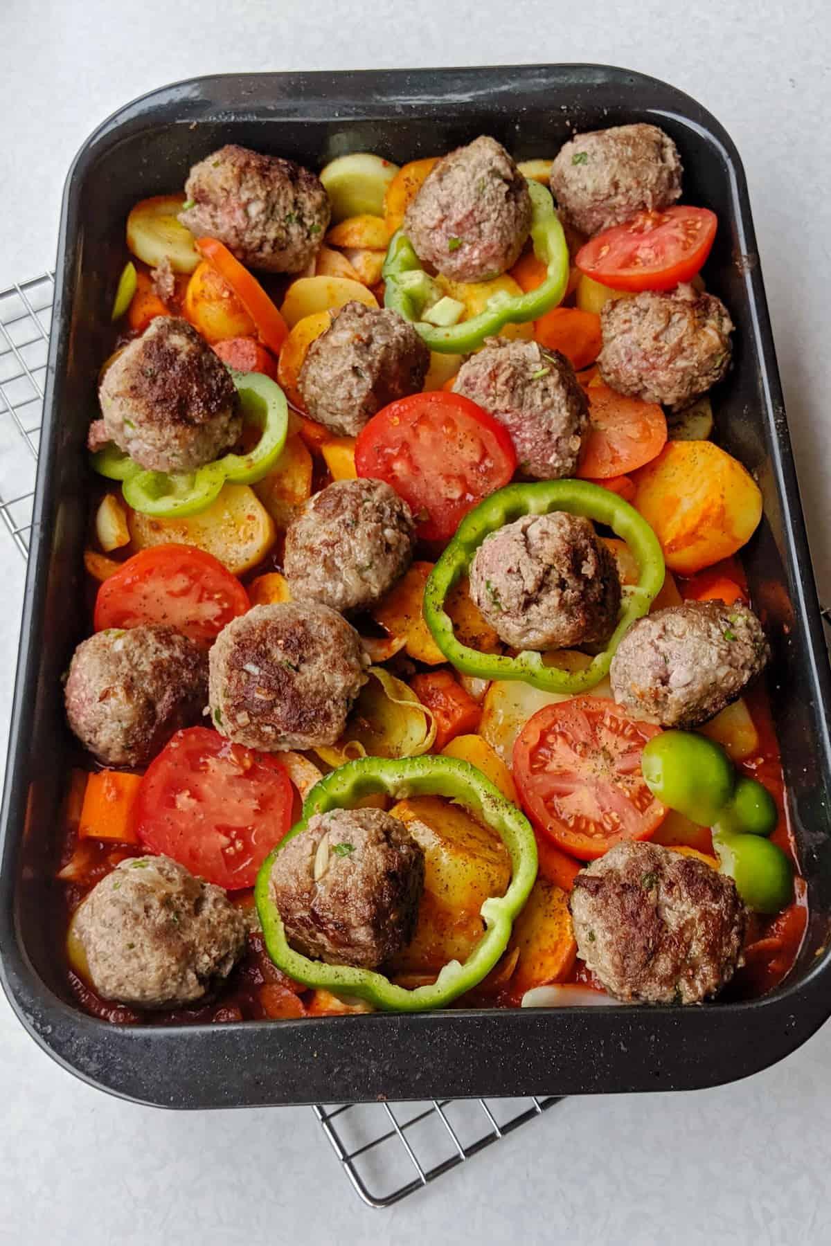 Eine Auflaufform mit den für den Ofen vorbereiteten gebackenen Kartoffeln in Tomatensoße mit Hackbällchen und Gemüse.