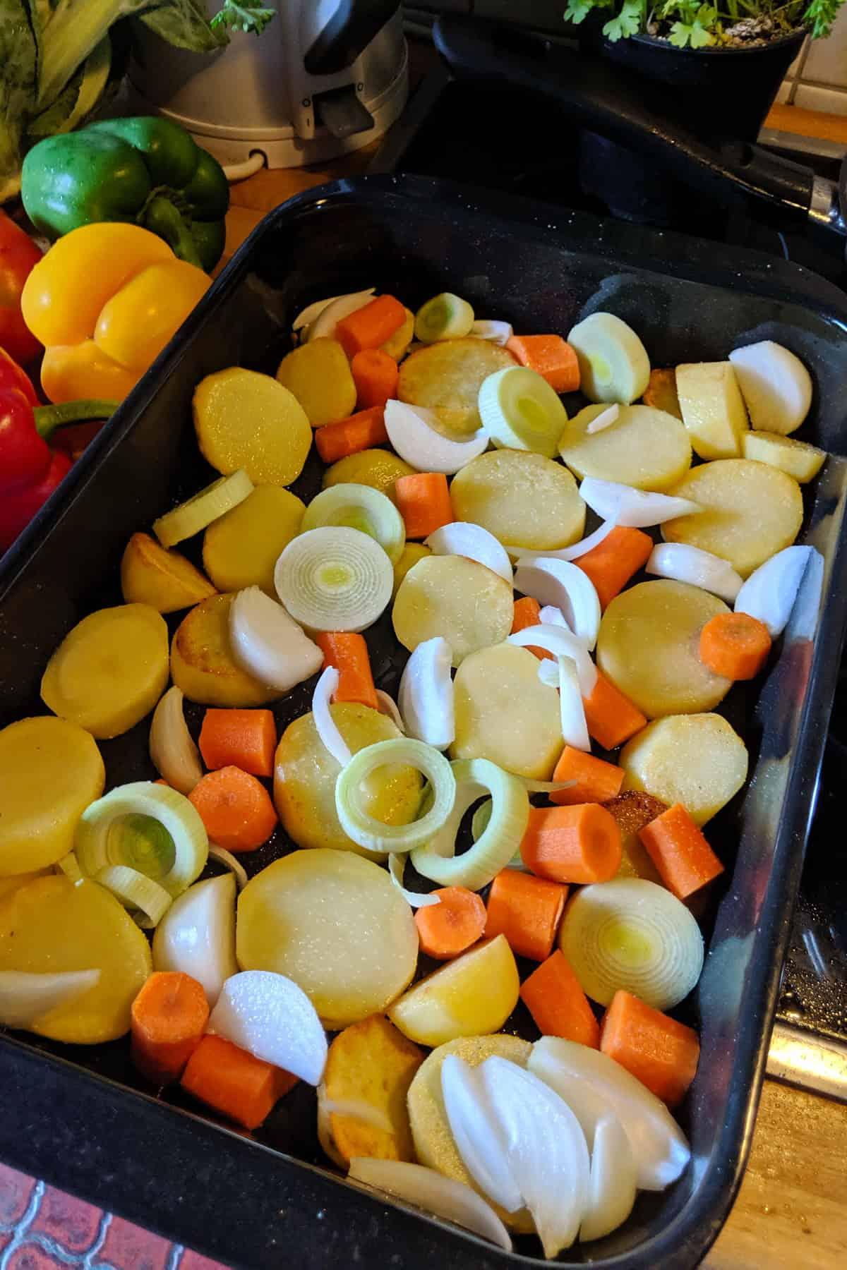 Die vorbereiteten Kartoffeln und das Gemüse in einer Auflaufform.