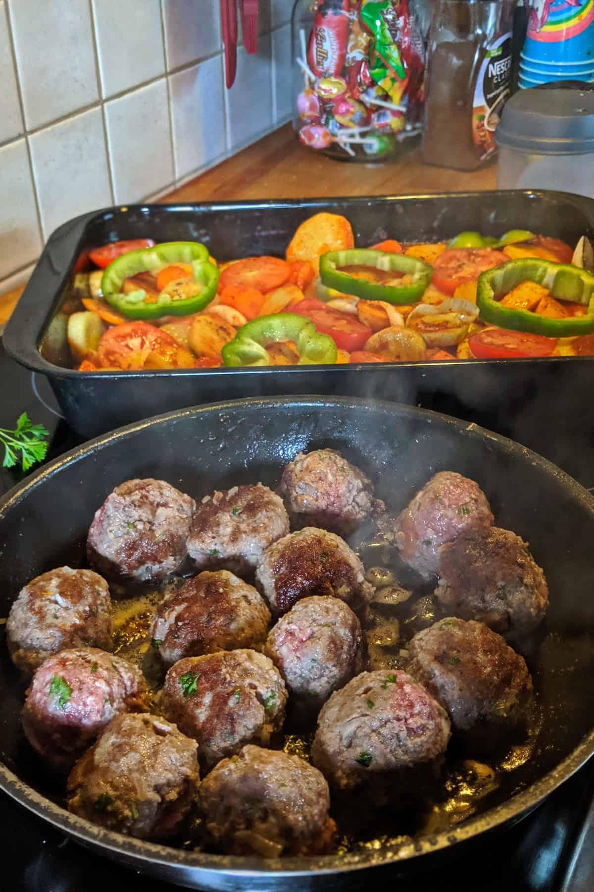 Zubereitung der gebackenen Kartoffeln in Tomatensoße mit Hackbällchen und Gemüse un der Küche.