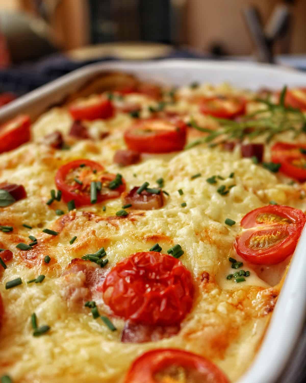 Eine Nahaufnahme einer weissen Auflaufform mit Kartoffel-Kohlrabi-Gratin mit Tomaten.
