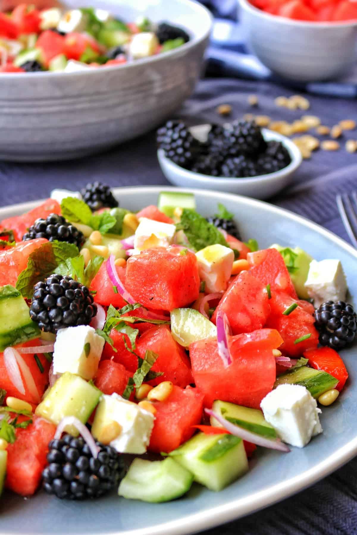 Ein Teller und eine Schüssel mit Melone-Feta Salat und Brombeeren.
