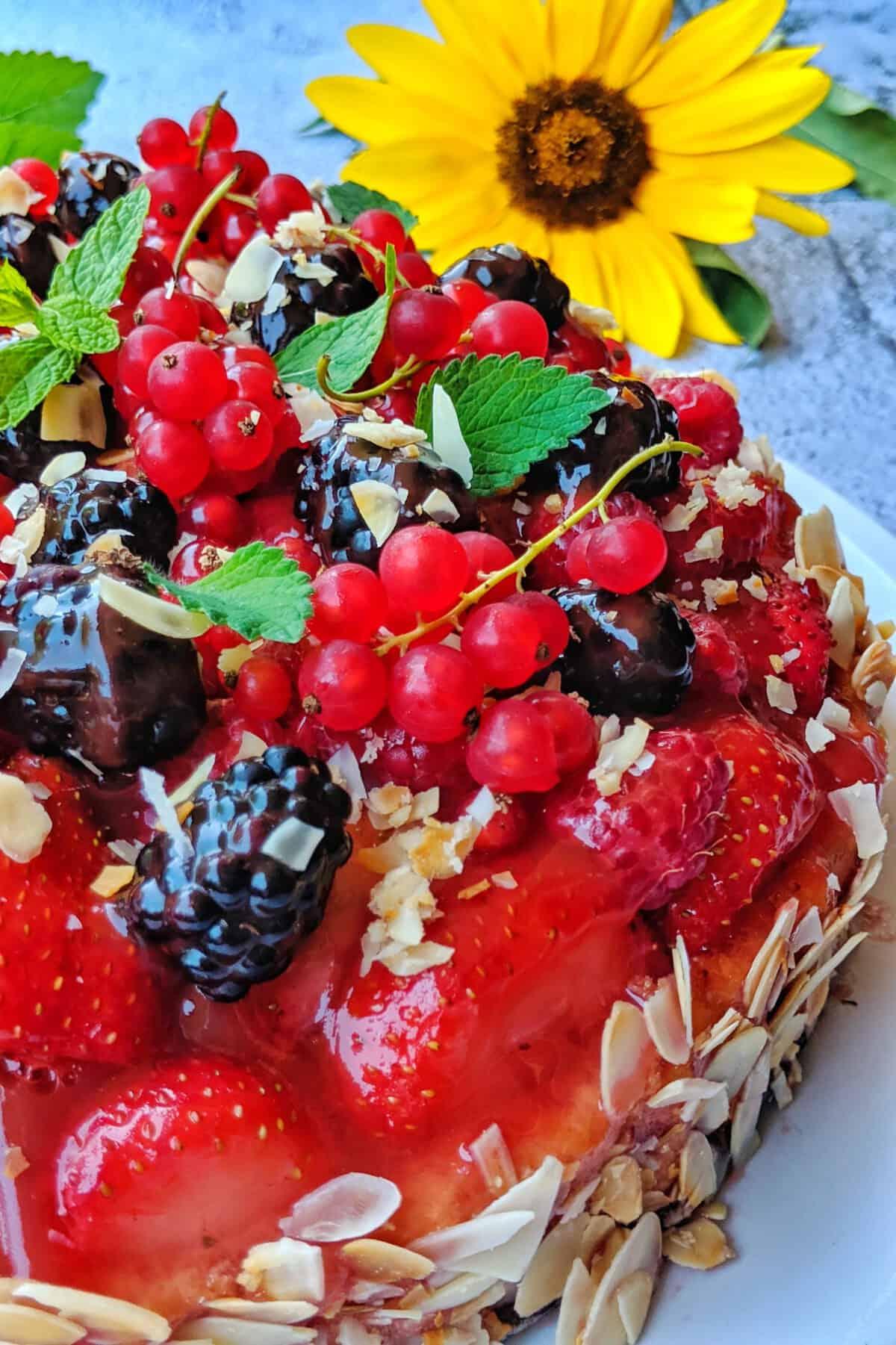 Eine Servierplatte mit einem Obstkuchen mit vielen bunten Fruechten. Dahinter Deko.