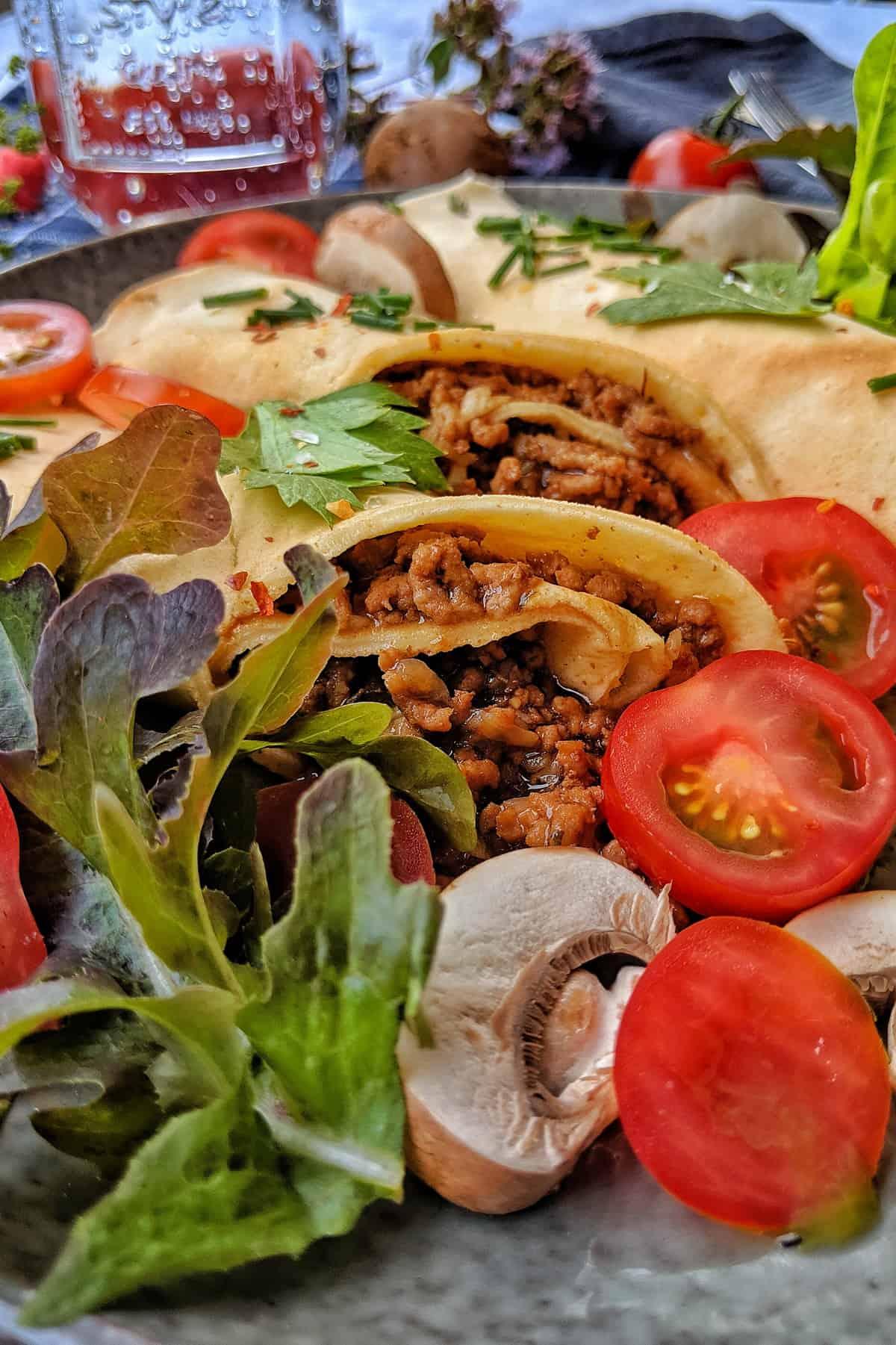 Eine Nahaufnahme von einem Teller mit herzhaften Pfannuchen sowie Tomaten und Salat.