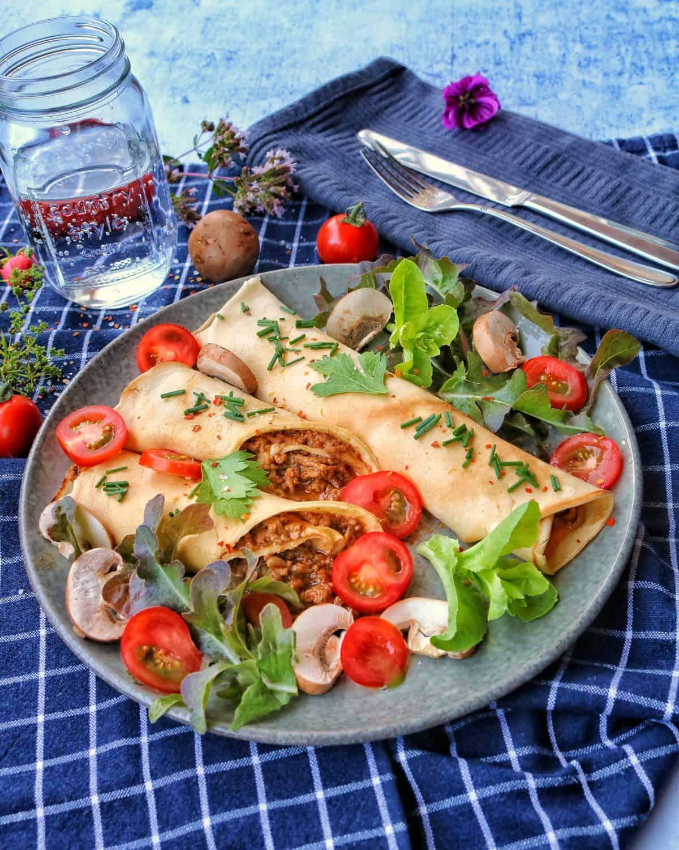 Ein Teller mit herzhaften Pfannuchen sowie Tomaten und Salat.