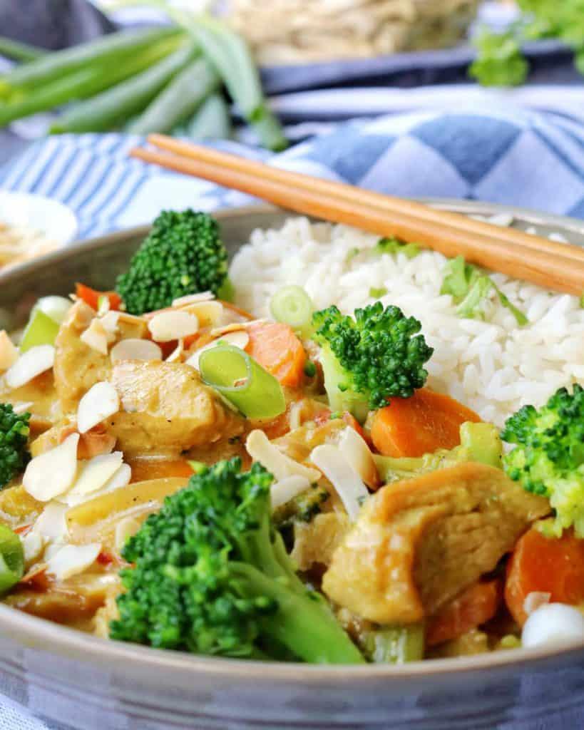 Eine Nahaufnahme von einem Teller mit Putencurry mit Brokkoli Mandeln und Reis