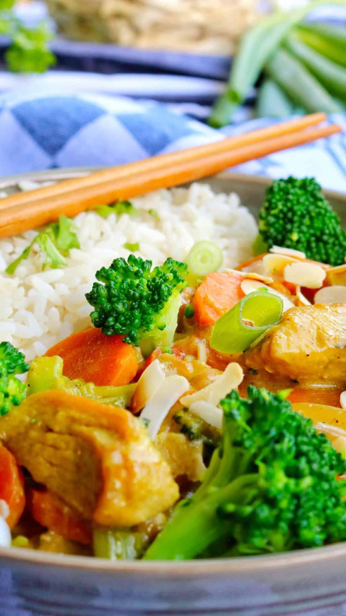 Eine Nahaufnahme von einem Teller Putencurry mit Brokkoli Mandeln und Reis