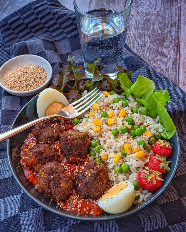 Eine Reis Bowl mit Hackbällchen und Tomatensoße