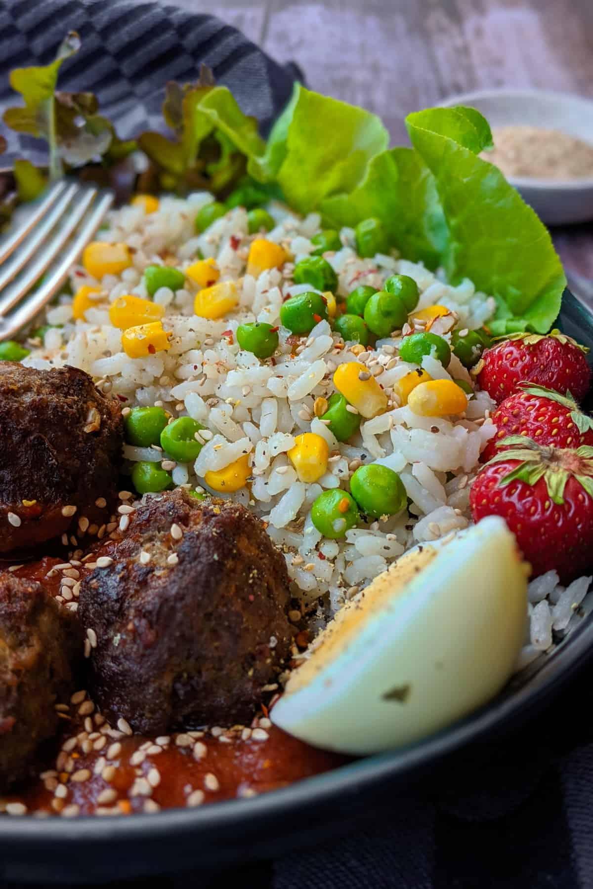 Eine Nahaufnahme von einer Reis Bowl mit Hackbällchen und Tomatensoße.