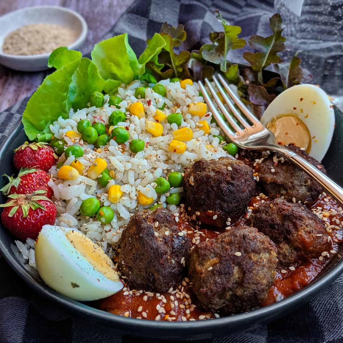 Eine Reis Bowl mit Hackbällchen und Tomatensoße.