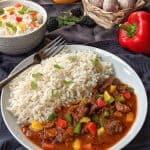 Ein weisser Teller mit Rindergulasch und Reis. Dahinter eine Schale Reis und Gemüse als Deko.