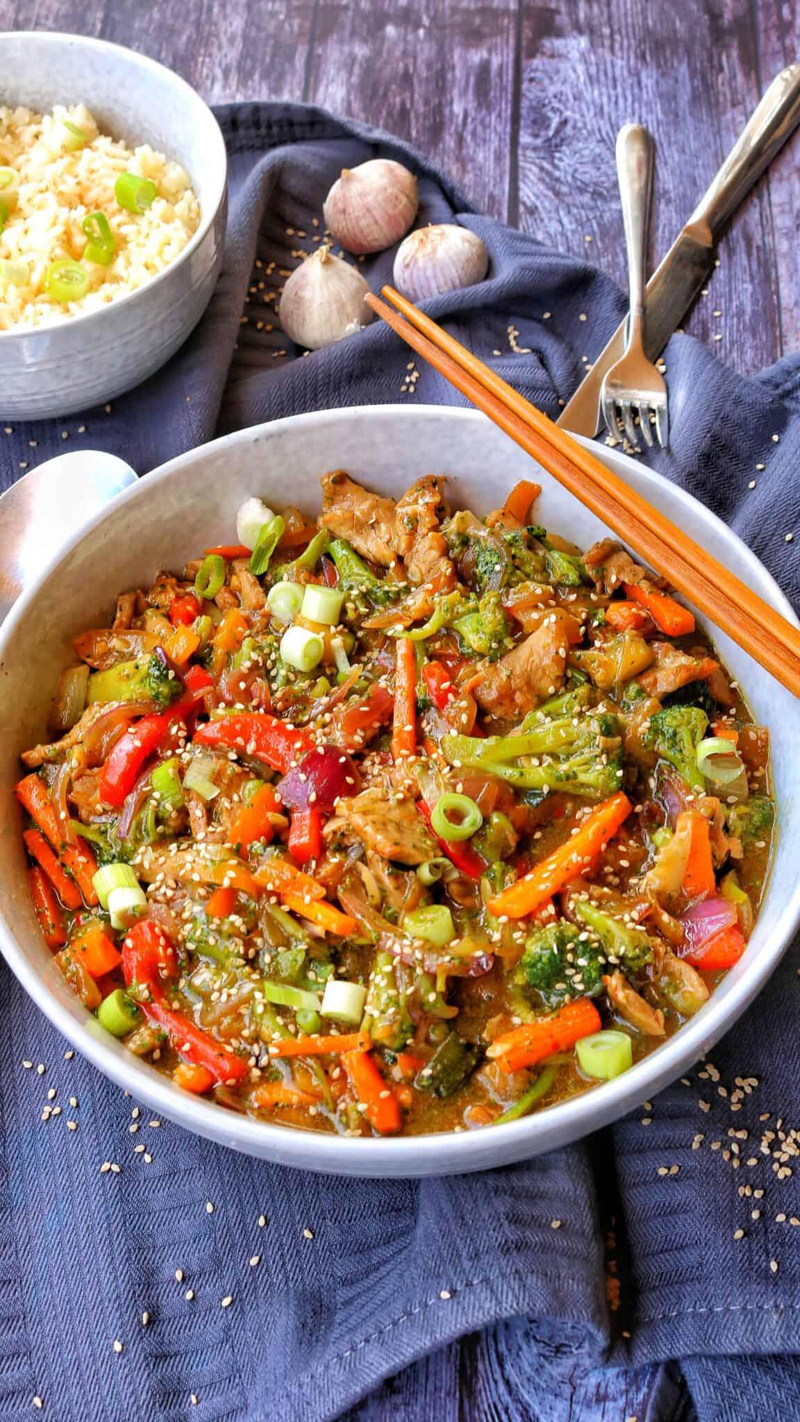 Eine helle Schalte mit der asia Pfanne mit Gemüse- Dahinter eine Schale mit Reis.