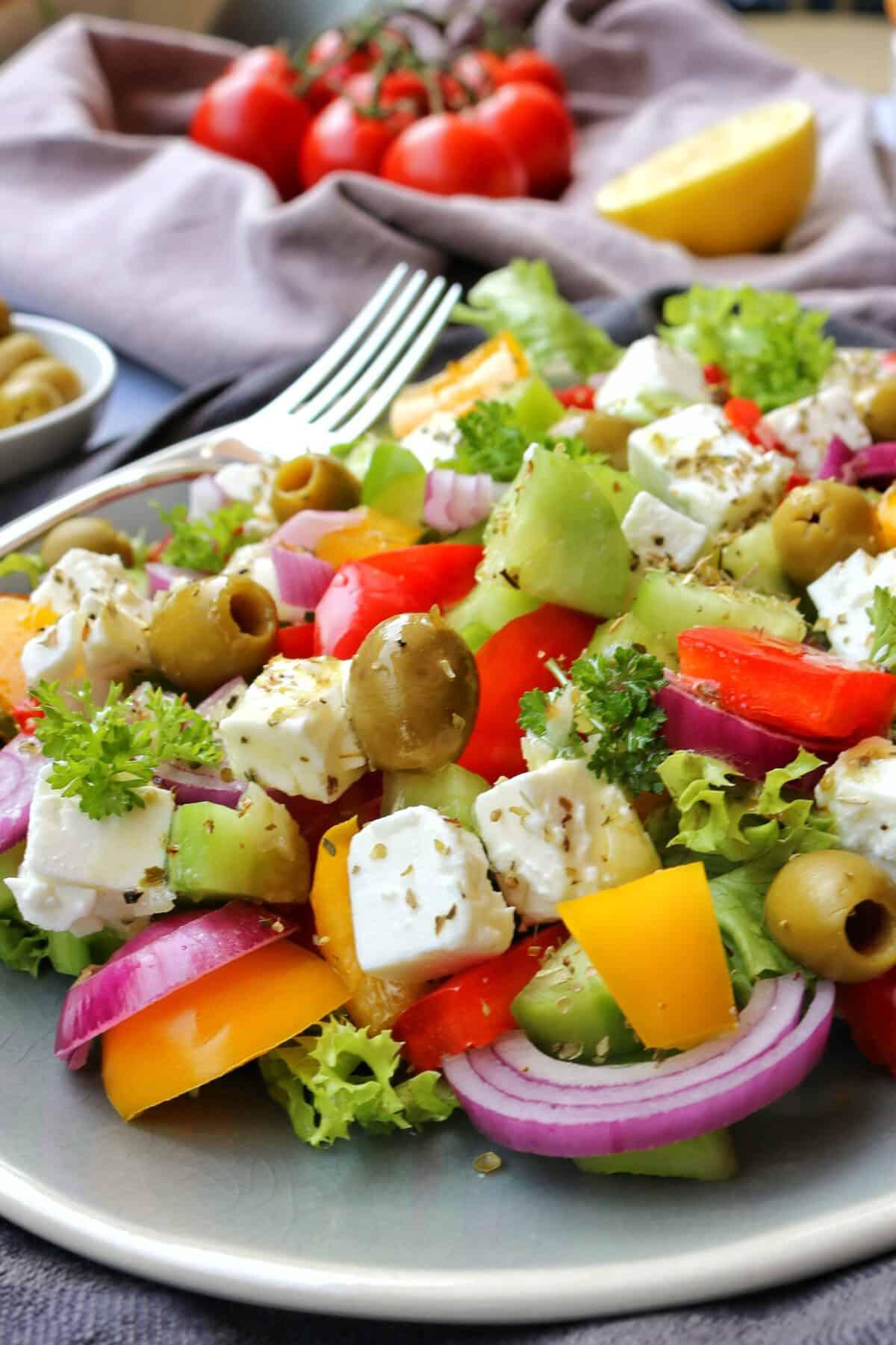 Griechischer Bauernsalat in einer Schüssel. Daneben Besteck und Deko
