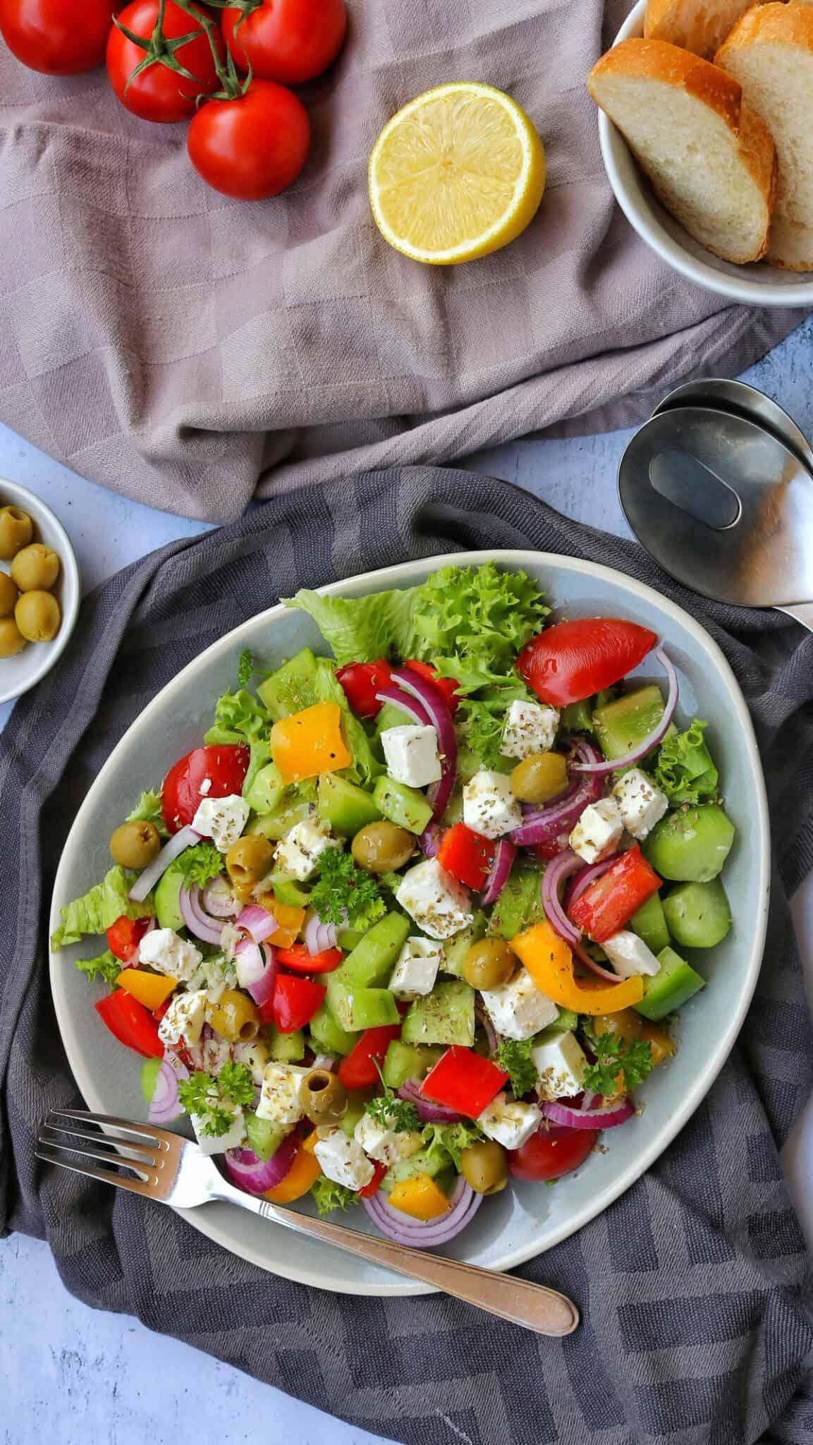 Ein Teller mit griechischem Bauernsalat. Darüber Oliven, Tomaten, Zitrone und Weissbrot als Deko.