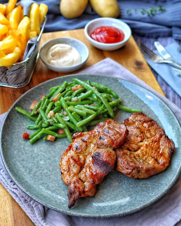 Ein Teller mit Nackensteak mit Speckbohnen und Pommes im Hintergrund