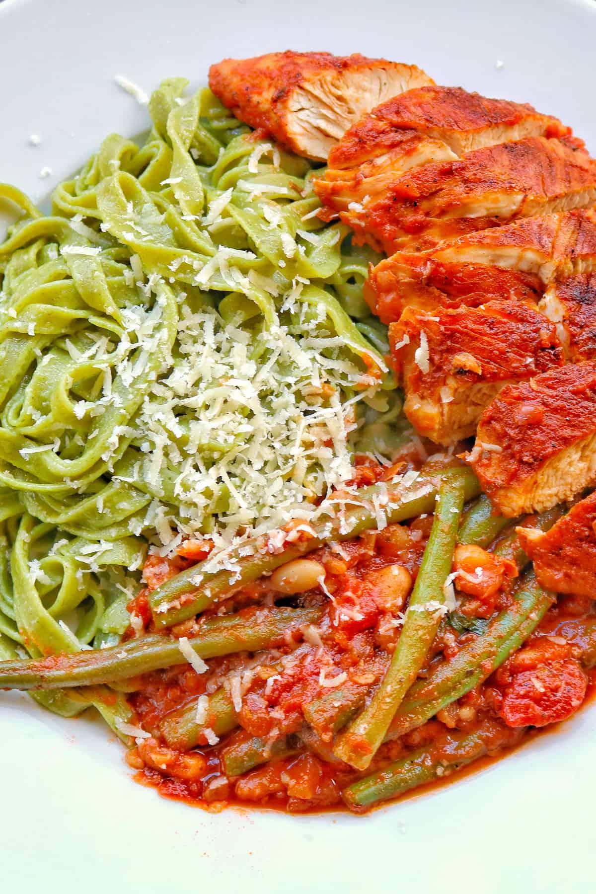 Ein Teller mit Putenbrust mit Bohnen in Tomatensoße. Dazu grüne Tagliatelle.