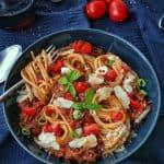 Einen Teller mit Spaghetti Bolognese und Deko