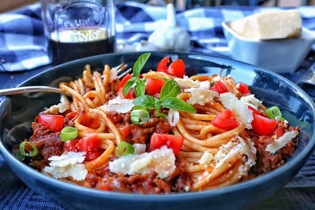 Ein tiefer, dunkler Teller mit Spaghetti Bolognese. Dahinter Knoblauch und ein halbvolles Glas als Dekoration.