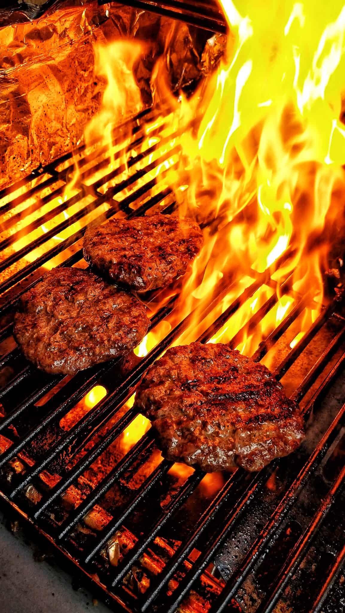 Burger auf einem Grill mit Flammen im Hintergrund.
