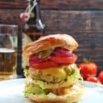 Ein doppelter Cheeseburger auf einem Teller. Im Hintergrund ein Bier
