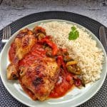 Einen Teller mit Huhn, Reis und Tomatensoße