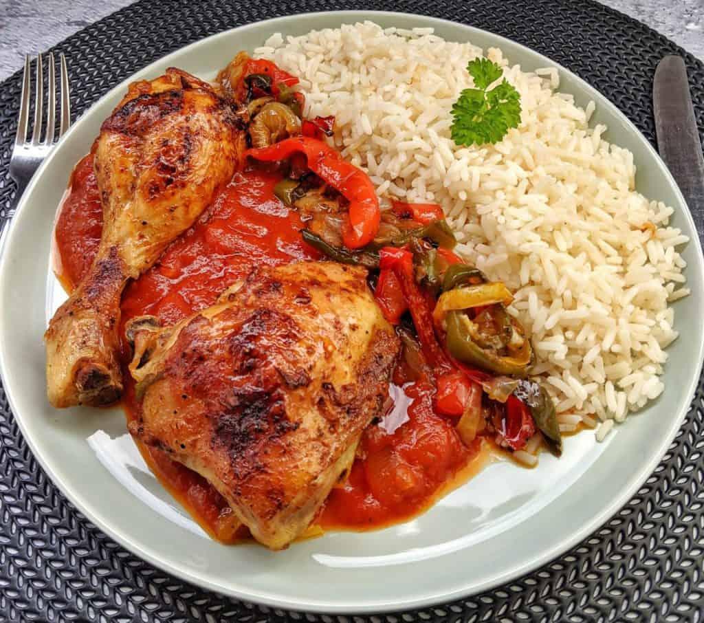 Ein Teller mit Huhn, Gemüse Tomatensoße und Reis
