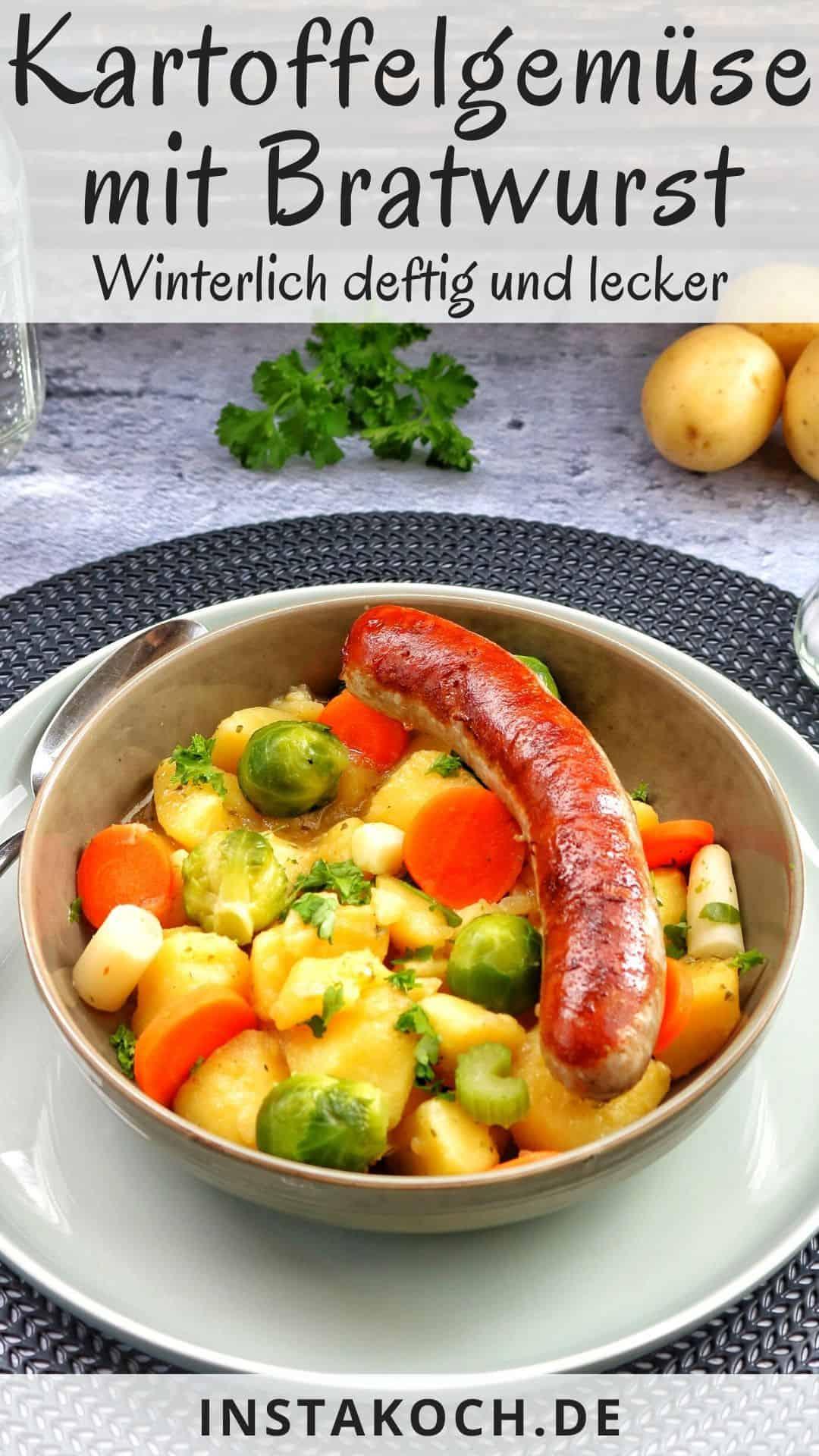 Eine Schale mit Kartoffelgemüse mit Bratwurst und Gemüse. Dahinter ein Glas Wasser und Gemüse als Deko.