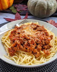 Ein tiefer weisser Teller mit Spaghetti und Bolognese Soße. In Hintergrund Deko.