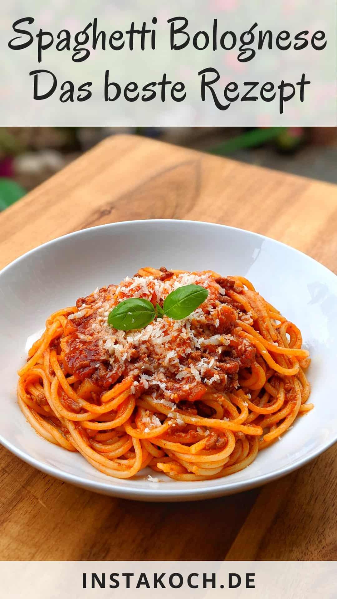 ein Teller mit Spaghetti Bolognese mit Parmesan und Basilikum Blättern.