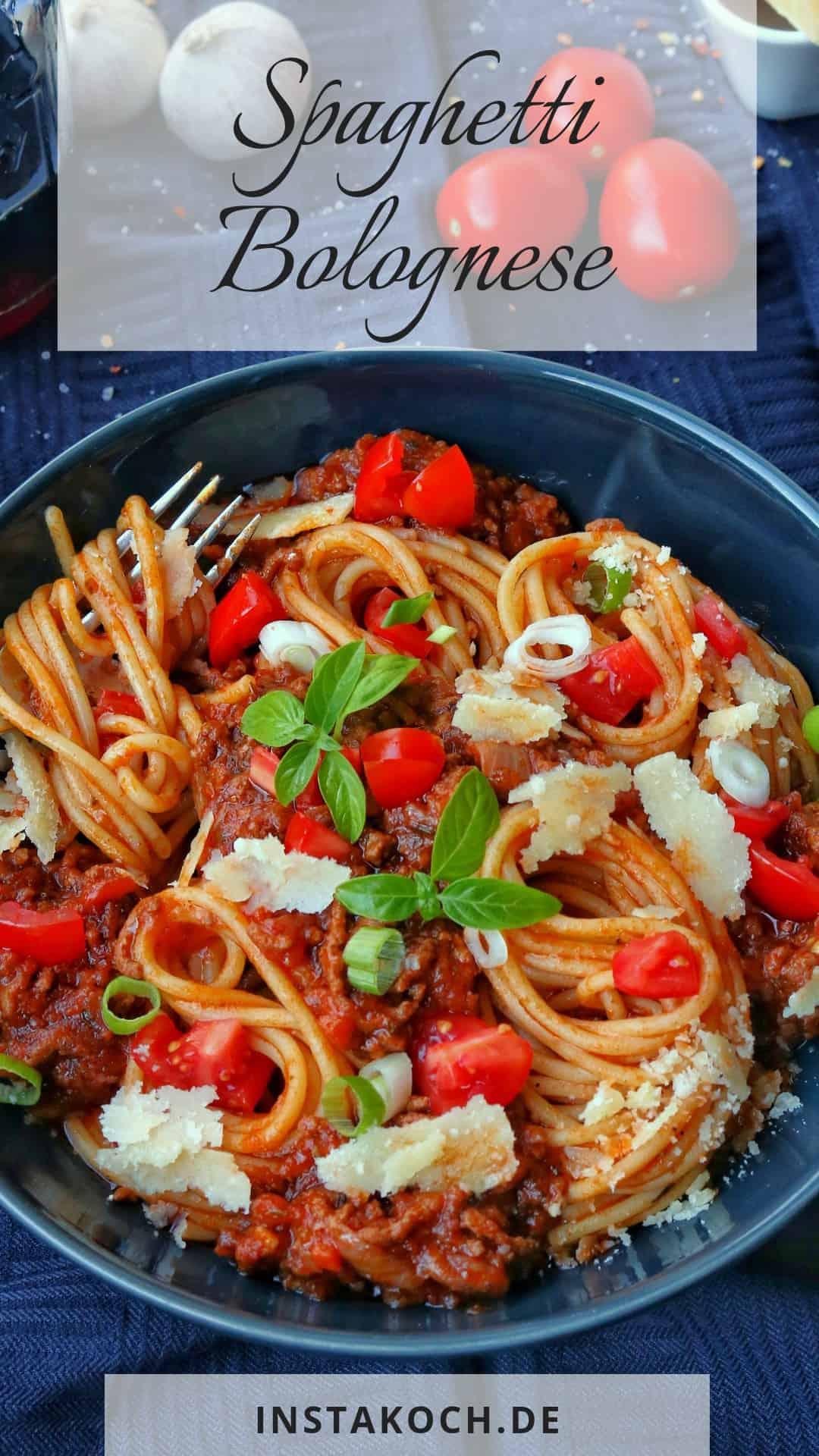 Ein tiefer, dunkler Teller mit Spaghetti Bolognese. Dahinter Tomaten und Knoblauch als Dekoration.