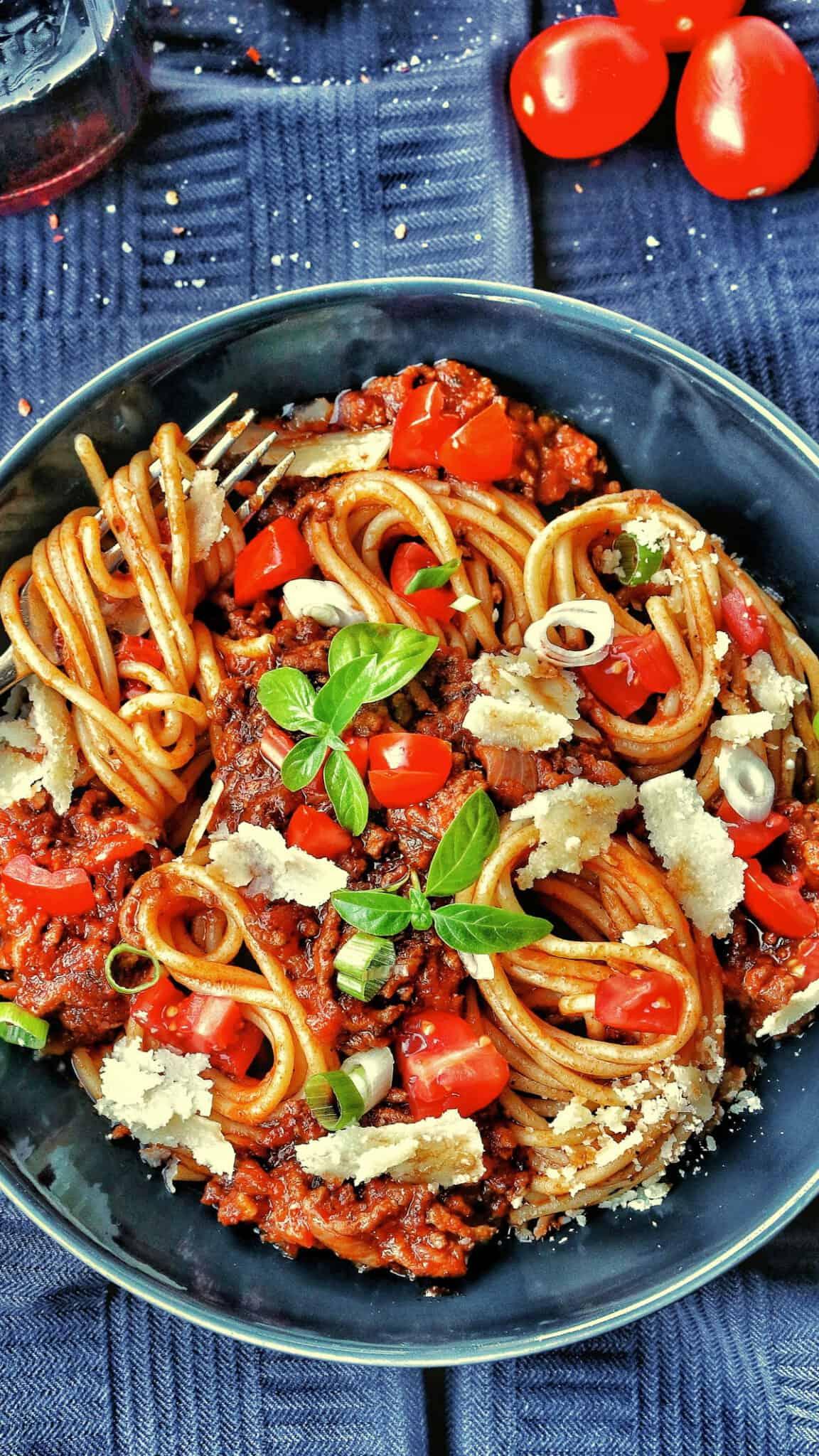 Ein Teller mit Spaghetti Bolognese mit Tomaten und Basilikum.