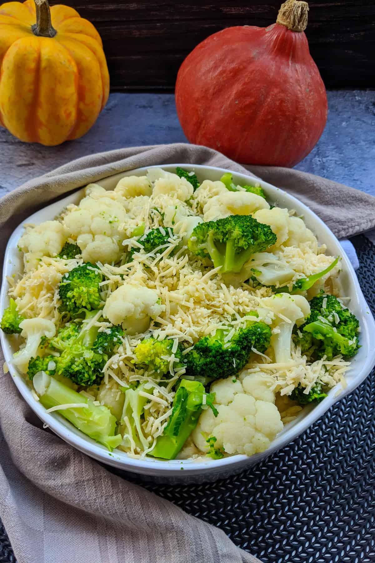 Vegetarischer Blumenkohl-Brokkoli Auflauf mit Kartoffeln und Lauch in einer weissen Auflaufform.